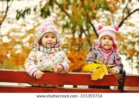two funny babies in fall time (focus on the left one) - stock photo