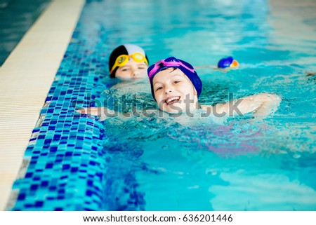 Two funny children smiling and swimming in sport pool indoors.