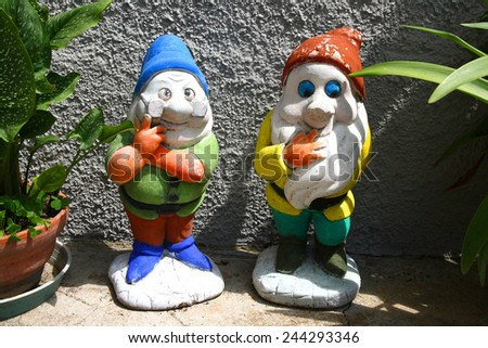 Two funny decorative dwarf in the garden - stock photo