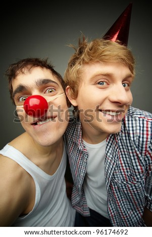 Two funny guys looking at camera and smiling crazily, fool's day series or birthday party - stock photo