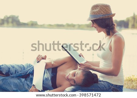 Two funny happy young women friends relaxing outdoors on green meadow on sunny spring summer day laughing enjoying good weather. Girl browsing internet on her mobile pad computer outside by the lake  - stock photo