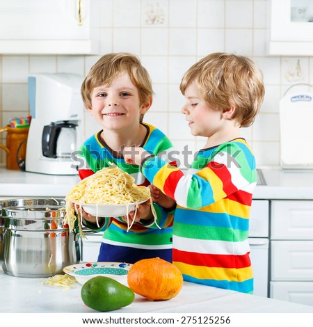 Two funny kid boys of 4 years cooking pasta and fresh vegetables in domestic kitchen, indoors. Sibling children in colorful shirts. - stock photo