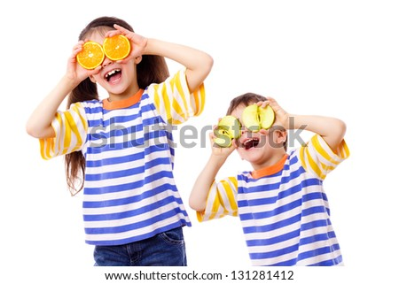 Two funny kids with fruits on eyes, isolated on white