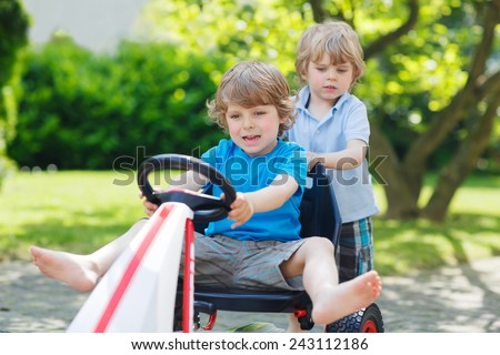 Two funny little boy friends having fun with toy race car in summer garden, outdoors. Active kid pushing the car with younger boy. Outdoor games for children in summer concept. - stock photo