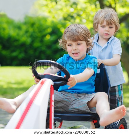 Two funny little boy friends having fun with toy race car in summer garden, outdoors. Active kid pushing the car with younger boy. Outdoor games for children in summer concept.