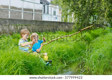 Two funny little brothers  fishing on a river with selfmade fishing rod  on sunny summer day. Happy children having fun. Active leisure for children outdoors. - stock photo