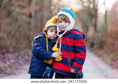 Two funny little kid sibling boys and friends hugging, on cold day, walking together in a park in spring, autumn or winter. Happy, joyful family. - stock photo