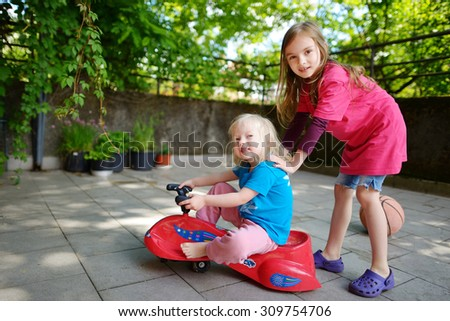 Two funny little sisters driving a toy car outdoors on beautiful summer day - stock photo