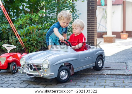 Two funny little toddler boys playing with big old toy car in summer garden, outdoors. Active leisure with kids on warm summer day. - stock photo
