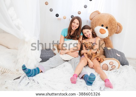 Two funny lovely sisters sitting and showing tongues in children room - stock photo