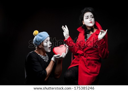 two funny mimes holding red heart isolated on black background