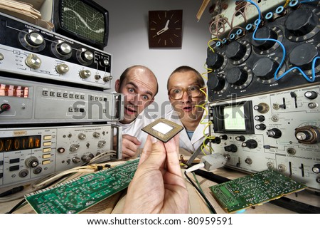 Two funny nerd scientists at vintage technological laboratory looking at modern computer processor