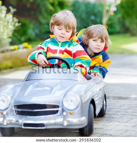 Two funny sibling kid boys playing with big old vintage toy car in spring or autumn garden, outdoors. Active leisure with kids outdoors  on warm spring or autumn day. - stock photo
