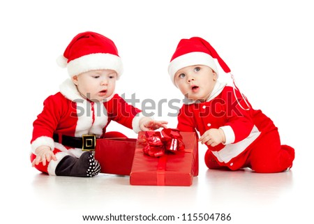 two funny small kids in Santa Claus clothes with gift box - stock photo