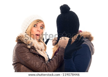 Two funny women in winter clothes having fun, isolated on white background.