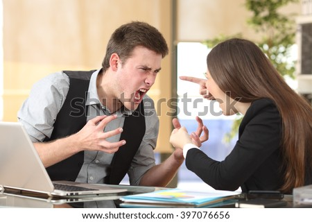 Two furious businesspeople arguing strongly in a desktop with an office background - stock photo