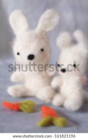 Two fuzzy rabbits overlook their fuzzy carrots. - stock photo