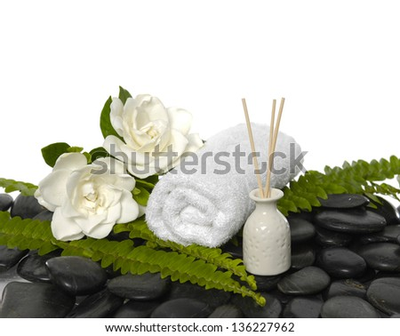 Two gardenia flowers with green fern and roller towel on black stones - stock photo