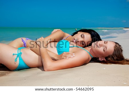 Two gay girls at the beach enjoying the sun - stock photo