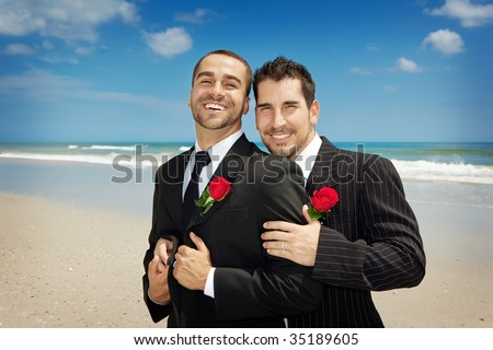 Two gay men looking into camera after a wedding ceremony - stock photo