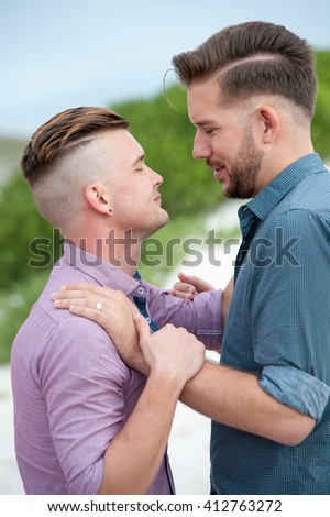 two gay men lovingly embrace and kiss next to a beach fence - stock photo