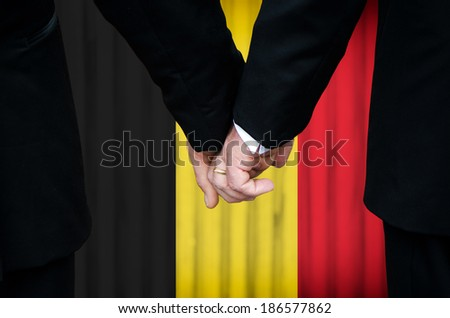 Two gay men stand hand in hand before a marriage altar featuring an overlay of the flag colors of Belgium, having just been legally married under the Same-Sex Marriage legislation of that country.   - stock photo