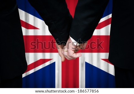Two gay men stand hand in hand before a marriage altar featuring an overlay of the Union Flag, having just been married within a United Kingdom country with legalized Same-Sex Marriage legislation.    - stock photo