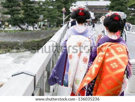 Two geisha walking on a bridge in Arashiyama, Japan - stock photo