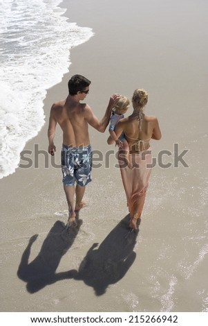 Two generation family walking along beach, woman carrying daughter (2-4), rear view, elevated view - stock photo