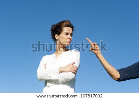 Two  generations, mother and daughter argueing, fighting, communicating. With one arm and finger pointing towards young girl. Isolated with blue sky as background and copy space. - stock photo