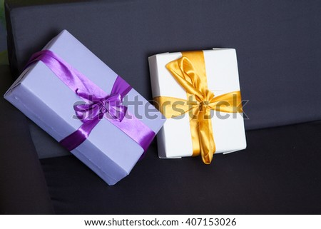 two gift boxes white and violet in studio - stock photo