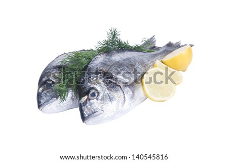 Two gilt-head fishes with lemon isolated on white - stock photo