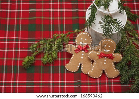 Two gingerbread man standing at the lantern with a candle on the traditional New Year's background. Copy space included for text. - stock photo