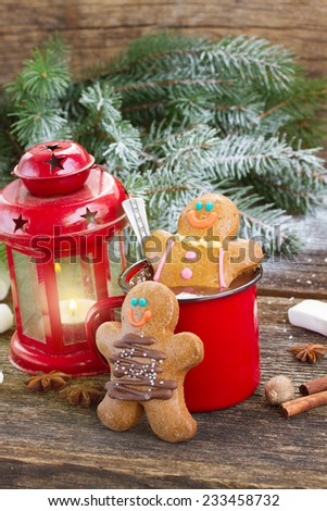 two  Gingerbread men with mug of  chocolate and glowing lantern on wooden background - stock photo