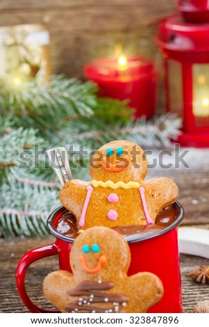 two  Gingerbread men with mug of  chocolate and glowing lanterns and christmas tree - stock photo