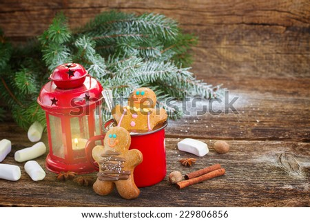 two  Gingerbread men with mug of hot chocolate and glowing lantern on wooden background - stock photo