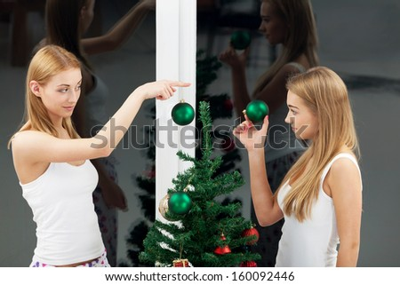 Two girl dressing up christmas tree - stock photo