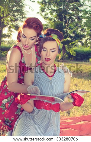 Two girl fashionista watch magazine retro style. - stock photo