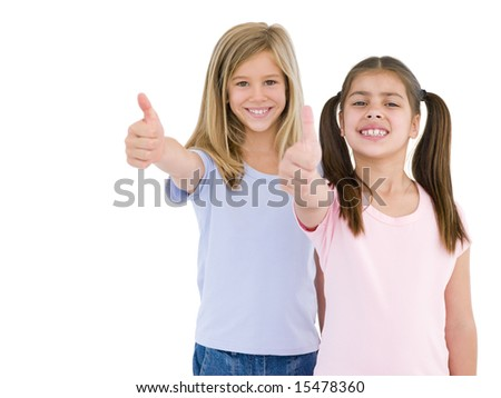 Two girl friends giving thumbs up smiling - stock photo