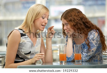 Two girl-friends gossip about guys in cafe - stock photo