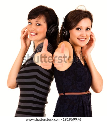 two girl friends in heaphones with thumbs up, white background - stock photo