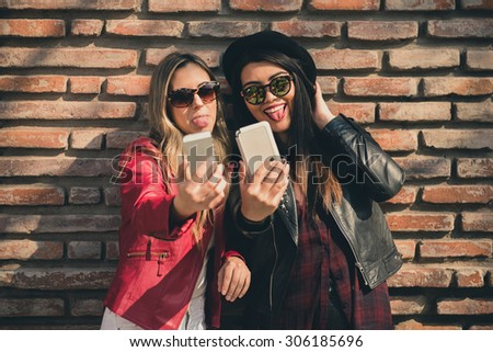 Two girl friends in the city taking a selfie with their smart phones - stock photo