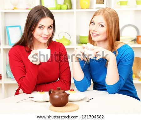 Two girl friends talk and drink tea in kitchen