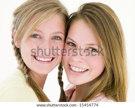 Two girl friends together smiling - stock photo