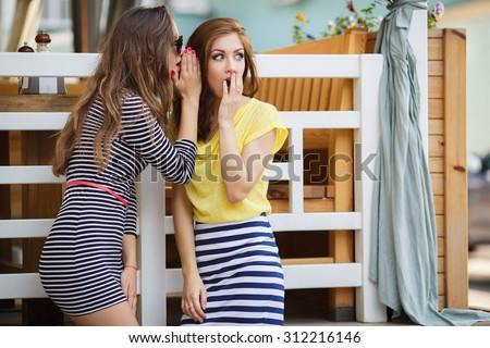 Two girl friends whispering secrets. summer holidays and vacation concept - girls gossiping . friendship, gossip and happiness concept - one girl telling another secret - stock photo