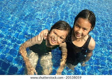 Two girl playing in the pool. - stock photo