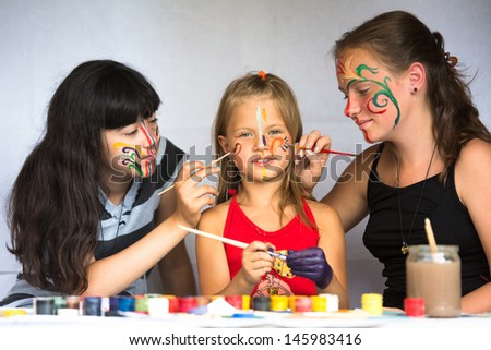 Two girl playing with painting with sister - stock photo