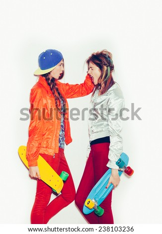 Two girl skaters go crazy and have fun together.  Beautiful sporty women Emotion.  Toned. White background, not isolated - stock photo