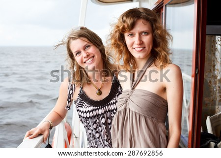 Two girlfriend have sea cruise on ship, standing at deck together
