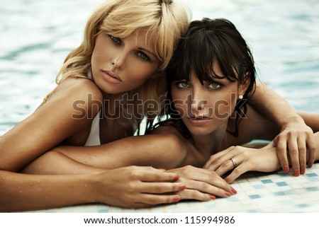 Two girlfriends enjoying the sun in a swimming pool while on vacation - stock photo